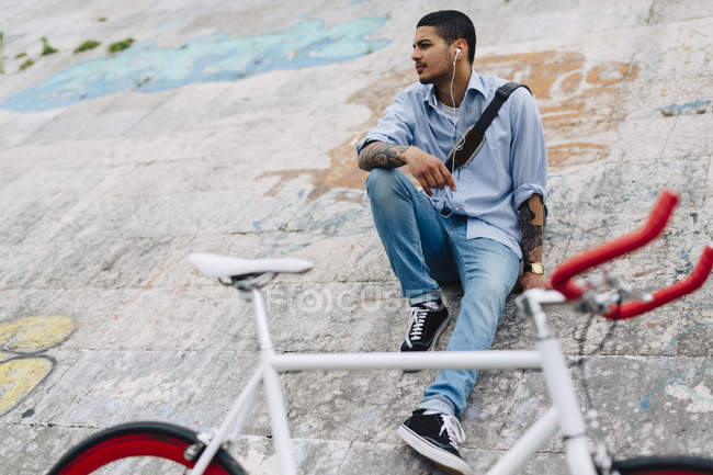 Young man with a bicycle sitting on a wall — Stock Photo