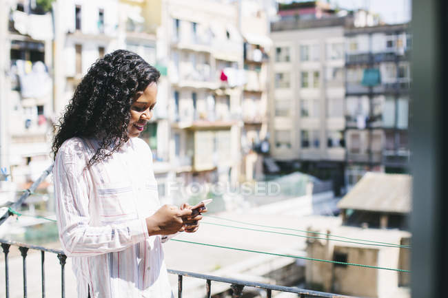 Young businesswoman standing on balcony and using smartphone — Stock Photo
