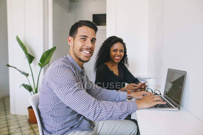 Young businessman and woman using laptop and smartphone in office — Stock Photo