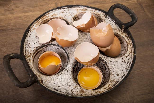 Старая сковорода яичных скорлуп с яичными желтками и пустыми яичными скорлупами на темном дереве — стоковое фото