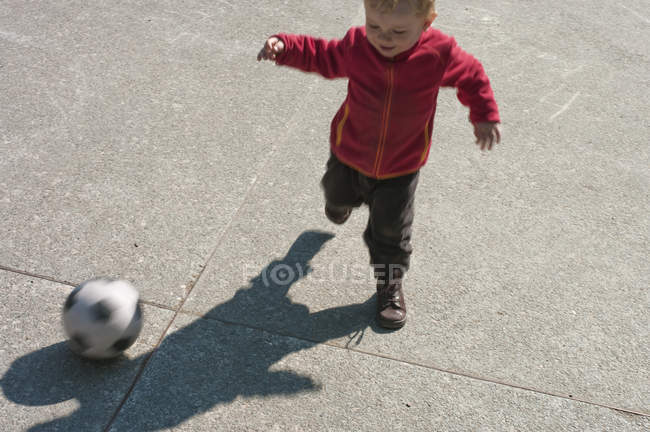 Baby boy playing soccer outdoors — Stock Photo