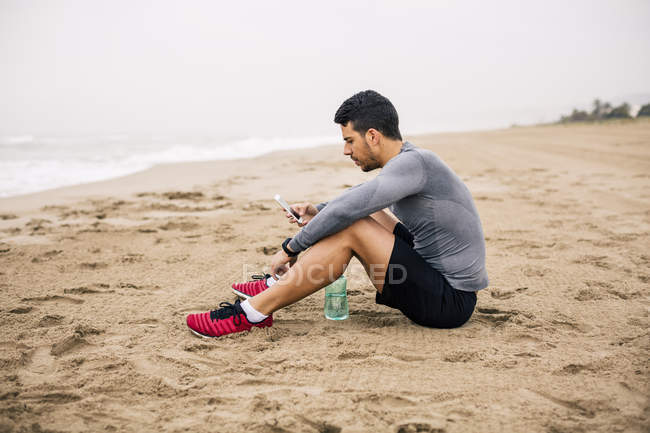 Sportive young man with cell phone and drinking bottle sitting on sandy beach — Stock Photo