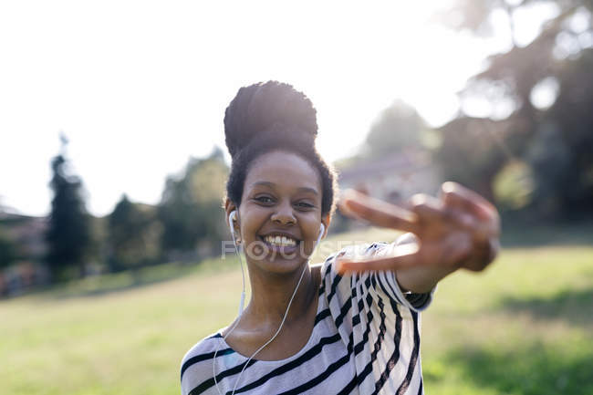 Portrait of happy woman hearing music with earphones showing victory sign — Stock Photo