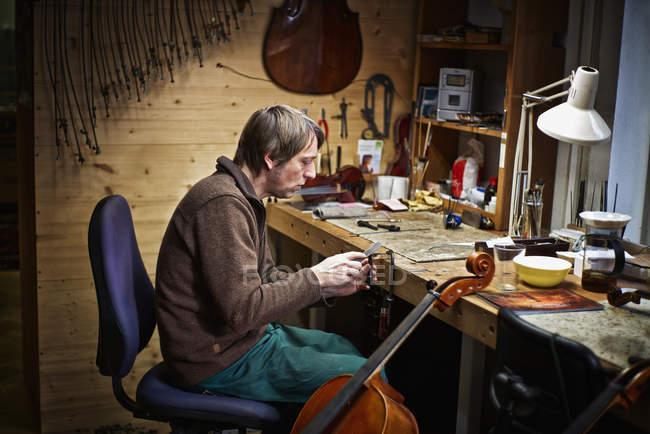 Geigenbauer feilt an einem Cello-Mechanismus in Werkstatt — Stockfoto