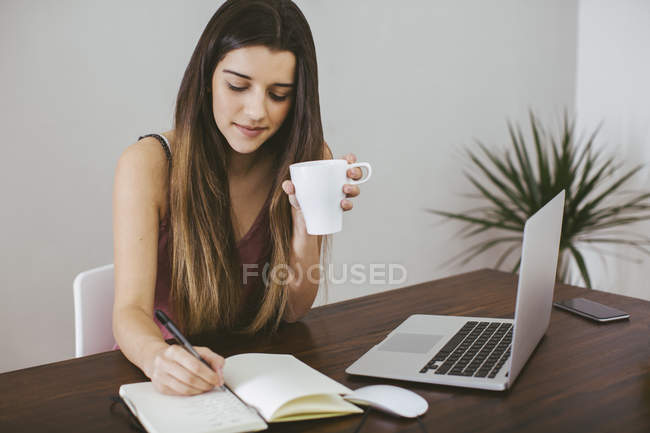 Молода жінка, робота на дому з ноутбук, ноутбук і чашкою кави — стокове фото