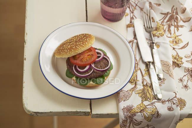 Hamburguesa con picadillo, tomate, lechuga de cordero y cebolla roja en el plato - foto de stock