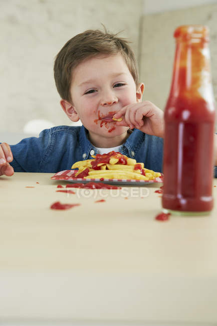 Niño comiendo papas fritas con ketchup - foto de stock