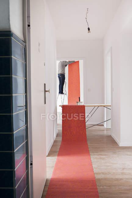 Людину, стоячи на сходах крок і обклеювання таблиці — стокове фото