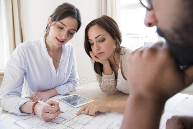 Colleagues discussing plan at table in office — Stock Photo