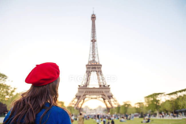France, Paris, Champ de Mars, back view of woman wearing red beret looking at Eiffel Tower — Stock Photo