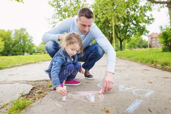 Батько і дочка креслення з тротуарна крейди — стокове фото