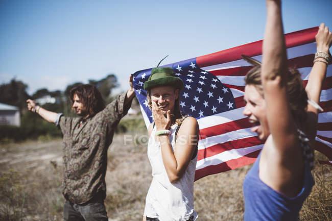 Bandera de tres hippies sin preocupaciones con nosotros en la naturaleza - foto de stock