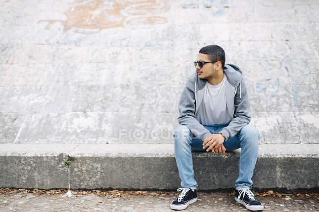Молодой человек, сидящий на стене в толстовке — стоковое фото