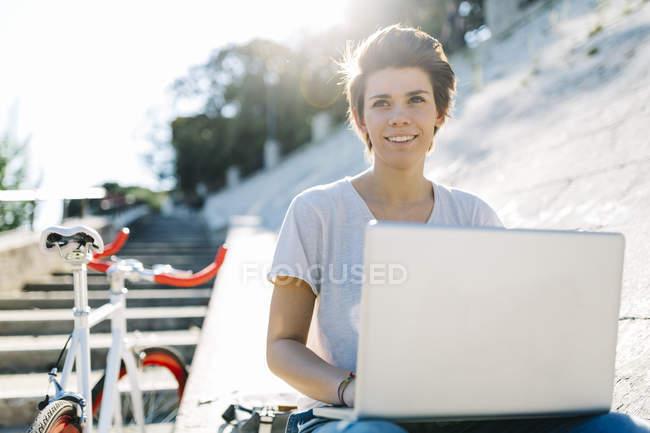 Mujer joven con bicicleta sentada al aire libre utilizando el ordenador portátil - foto de stock