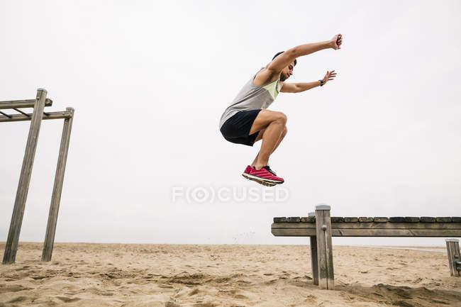 Young man training long jump on beach — Stock Photo