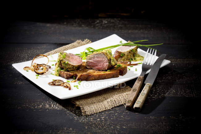 Fillet of pork on crusty bread with mustard herb butter and rucola on white  plate — Stock Photo