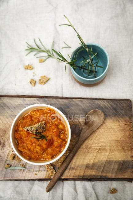 Vegetarian chili sauce in bowl on wooden board with wooden spoon — Stock Photo
