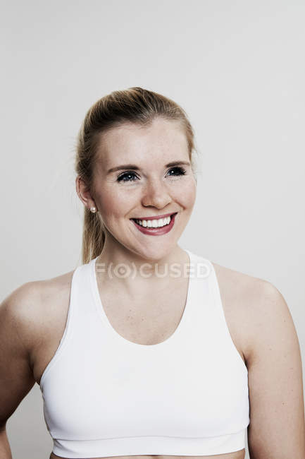 Портрет улыбается женщина перед светлый фон — стоковое фото