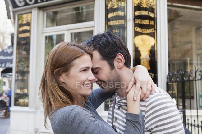 Casal apaixonado, abraçando-se na frente de pastelaria — Fotografia de Stock