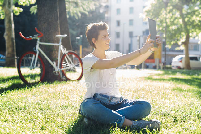 Sorrindo jovem mulher sentada no prado tirando uma selfie com tablet digital — Fotografia de Stock