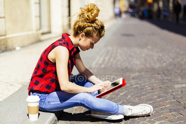 Italy, Verona, woman sitting on curb using digital tablet — Stock Photo