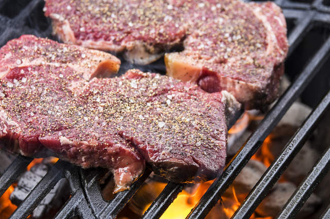 Beef steaks grilling over charcoal on barbecue grill — Stock Photo