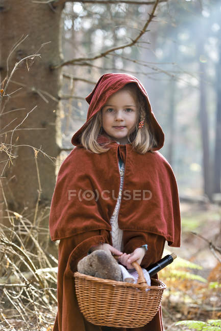 Portrait of little girl masquerade as Red Riding Hood standing in the wood — Stock Photo