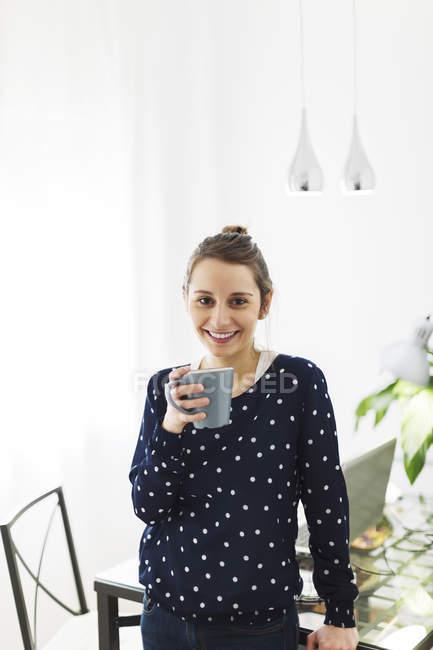 Retrato de jovem com caneca em casa — Fotografia de Stock