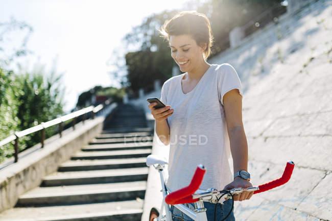Giovane donna sorridente con bicicletta e cellulare — Foto stock