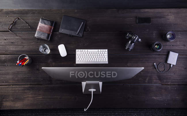 Desk with computer and camera — Stock Photo