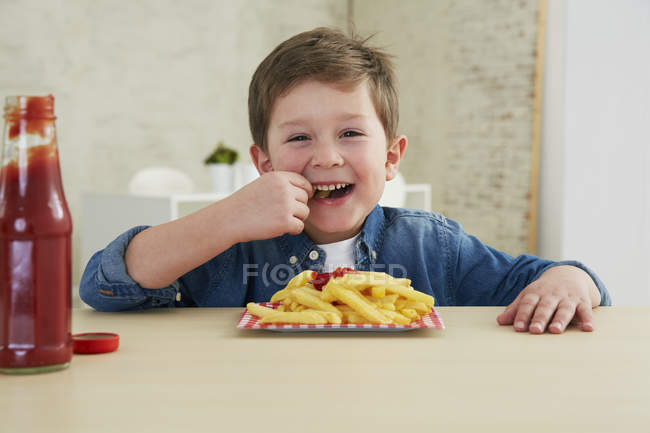 Boy eating French fries with ketchup — Stock Photo