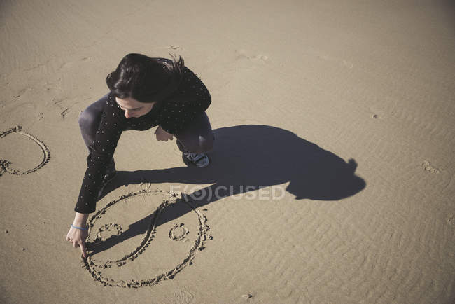 Mulher coçando o símbolo Yin Yang na areia de uma praia — Fotografia de Stock