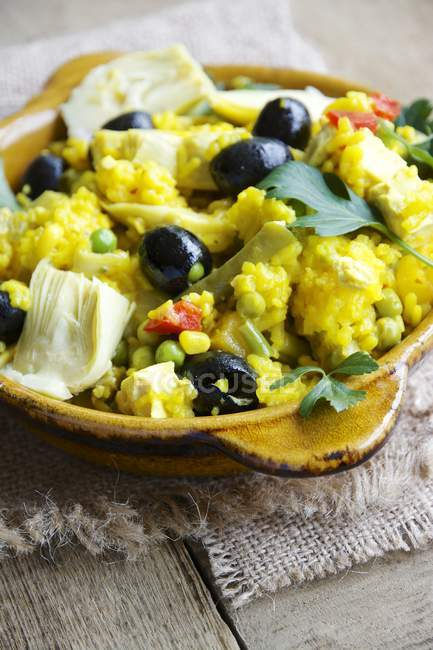 Vegetarian paella with artichoke, black olives, green beans and red bell pepper — Stock Photo