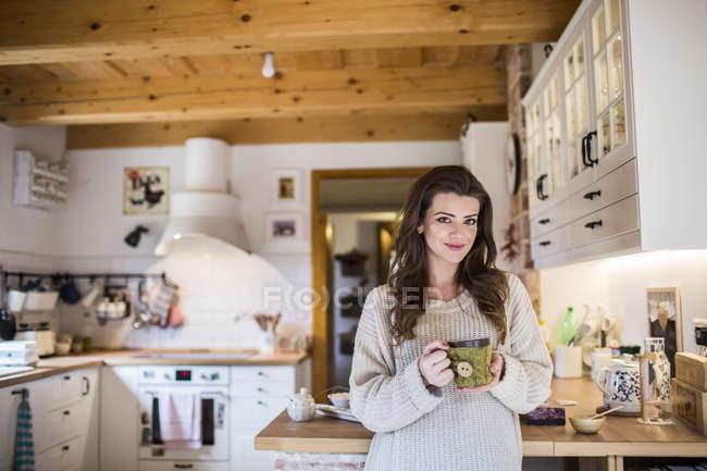 Jeune femme à la maison boire la tasse de café dans la cuisine — Photo de stock