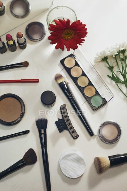 White makeup table with various of cosmetics and flowers, top view — Stock Photo