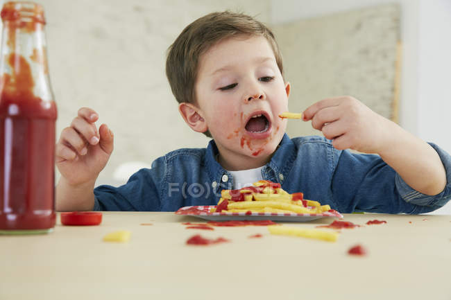 Garçon, manger Français frites avec du ketchup — Photo de stock