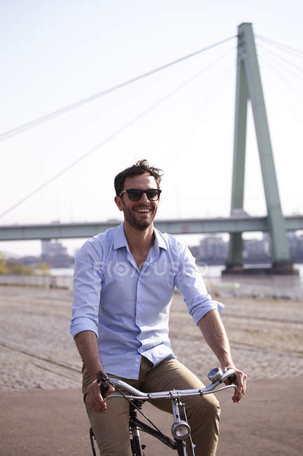 Adult man riding bicycle on riverbank — Stock Photo