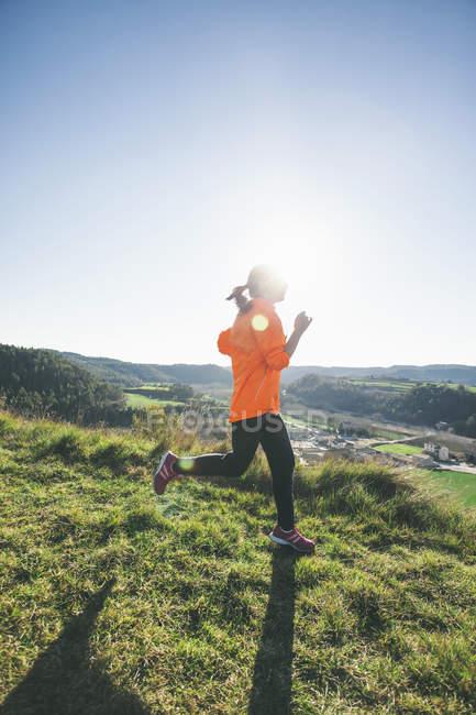 Jogger mujer joven en movimiento en contraluz - foto de stock