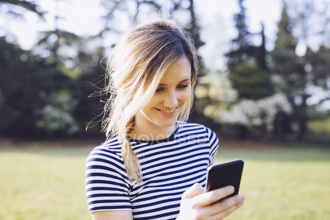 Portrait of smiling blond woman looking at her smartphone — Stock Photo