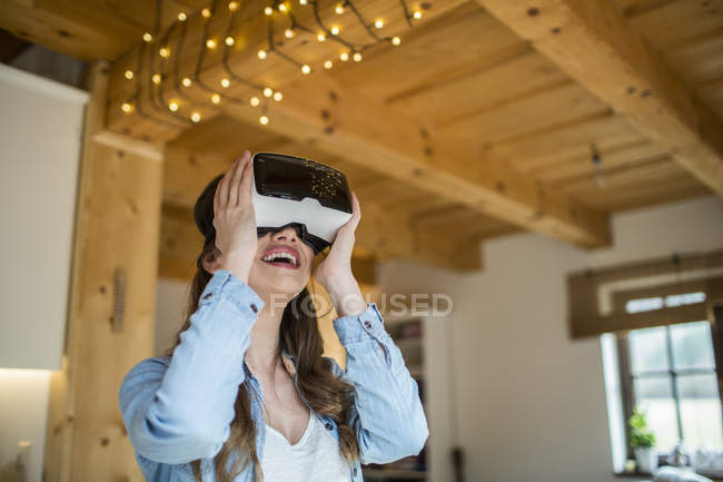 Young woman at home using Virtual Reality goggles — Stock Photo