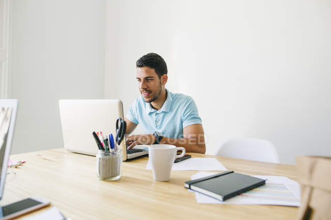 Young man using laptop at desk in office — Stock Photo