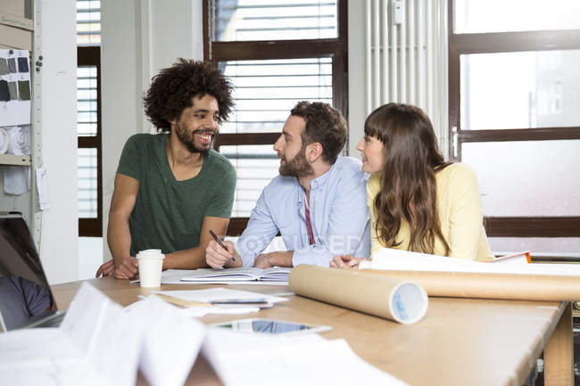 Three creative professionals sitting together in office — Stock Photo