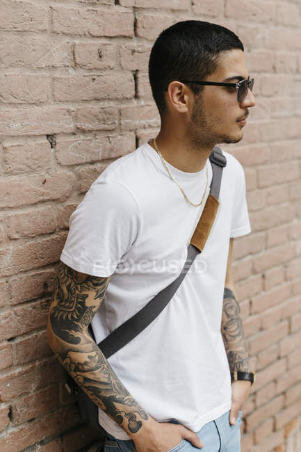 Young man leaning against a brick wall — Stock Photo