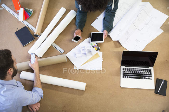 Two colleagues with portable devices surrounded by construction plans — Stock Photo