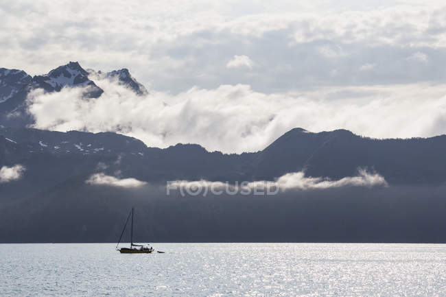 USA, Alaska, Seward, Resurrection Bay, view to mountains and sailing boat in front — Stock Photo