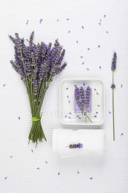 Lavender, white towel, lavender soap on soap basket — Stock Photo