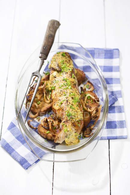 Solomillo de cerdo en pan crujiente con mantequilla de hierbas mostaza y rúcula, en una cazuela - foto de stock