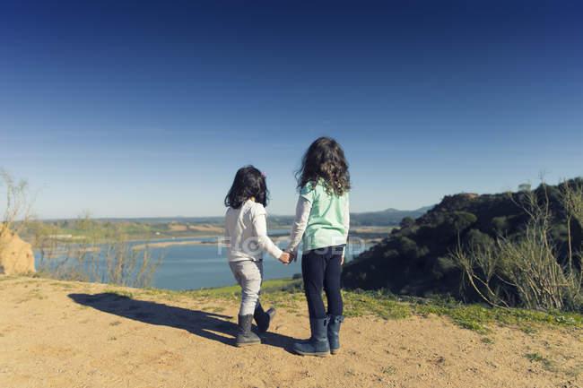 Испания, Бурухон, две маленькие девочки смотрят на озеро — стоковое фото