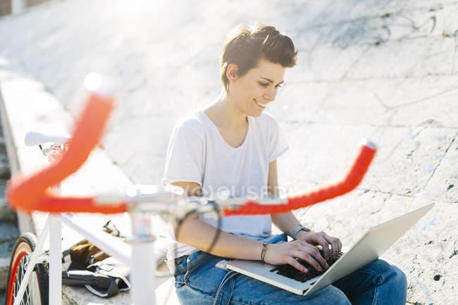 Jovem com bicicleta sentada ao ar livre usando laptop — Fotografia de Stock