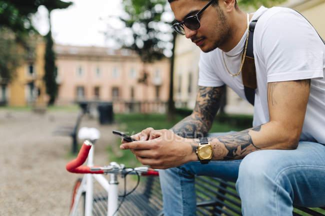 Giovane seduto sulla panchina a guardare il cellulare — Foto stock